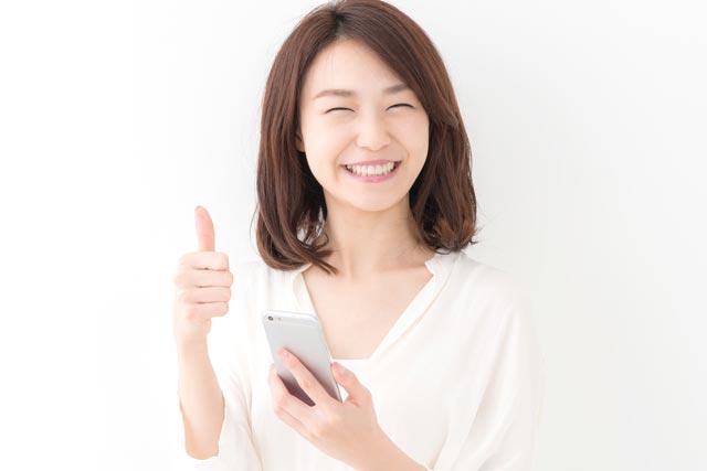 LINEモバイル片手に喜ぶ女性